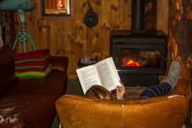 reading a book by the fire at Bruny Island Lodge