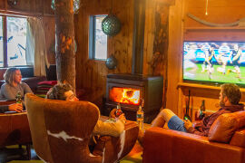 relaxing by the fire and watching footy at Bruny Island Lodge